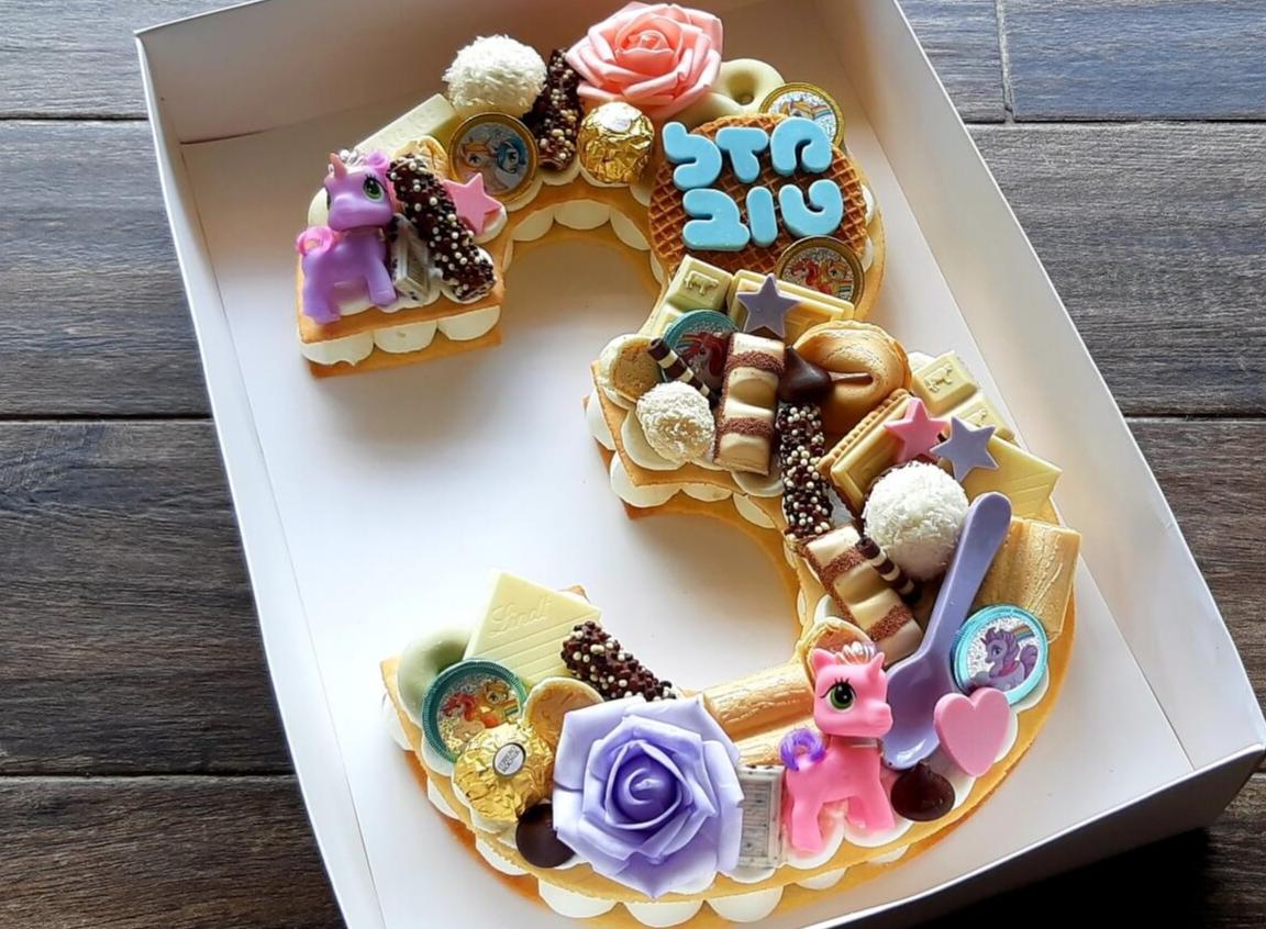 עוגת חד קרן גיל 3 - שתי שכבות בצק שקדים פריך במילוי קרם מסקרפונה ווניל אמיתי עם כל השוקולדים הכי חמים<br>בתוספת מטבעות שוקולד ממותגות, בובות חד קרן והקדשה אישית.