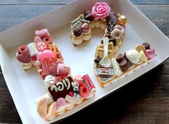 עוגת מספרים 12 (בת מצווה) - שתי שכבות בצק שקדים פריך במילוי קרם מסקרפונה ווניל אמיתי עם שוקולד מובחר בתוספת נשיקות מרנג, ממתקים חמוצים ועוד...