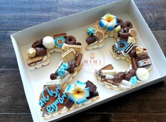 עוגת מספרים 23 פרחונית וכחולה - שתי שכבות בצק שקדים פריך במילוי קרם מסקרפונה ווניל אמיתי עם שוקולד מובחר <br>בתוספת פופקורן מקורמל והקדשה אישית.<br>