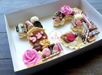 עוגת מספרים 13 פרחונית וורודה - שתי שכבות בצק שקדים פריך במילוי קרם מסקרפונה ווניל אמיתי עם שוקולד מובחר <br>בתוספת פופקורן מקורמל מקרונים והקדשה אישית.<br>