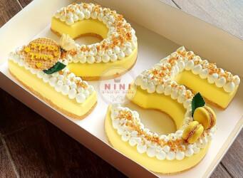 עוגת מוס מספרים 25 - בסיס עוגיות חמאה, מוס לימון וקרם קוקוס בתוספת מקרונים והקדשה אישית