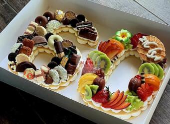 עוגת מספרים 60 - שתי שכבות בצק שקדים פריך במילוי קרם מסקרפונה ווניל אמיתי עם תותים קיווי ועוד.<br>בתוספת שוקולד מובחר, מקרונים מטריפים, בקבוק ויסקי והקדשה אישית