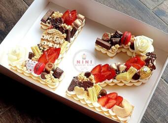 עוגת מספרים 12 (בת מצווה) - מתוק בתוספת המון אדום<br>שתי שכבות בצק שקדים פריך במילוי קרם מסקרפונה ווניל אמיתי מפוצצת בשוקולד מובחר, בתוספת מקרונים.