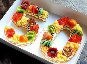 עוגת מספרים 50 - שתי שכבות בצק שקדים פריך במילוי קרם מסקרפונה ווניל אמיתי עם תותים, אננס פסיפלורה ועוד, בתוספת מקרונים ירוקים ומטריפים