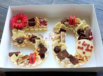 עוגת מספרים 50 - שתי שכבות בצק שקדים פריך במילוי קרם מסקרפונה ווניל אמיתי עם שוקולד מובחר<br>בתוספת מקרונים, פופקורן מקורמל והקדשה אישית.