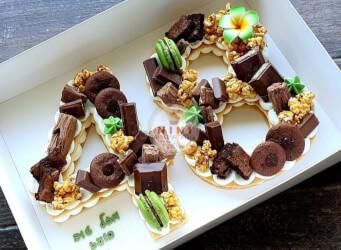 עוגת מספרים 48 - שתי שכבות בצק שקדים פריך במילוי קרם מסקרפונה ווניל אמיתי עם שוקולד מובחר<br>בתוספת מקרונים, פופקורן מקורמל והקדשה אישית.